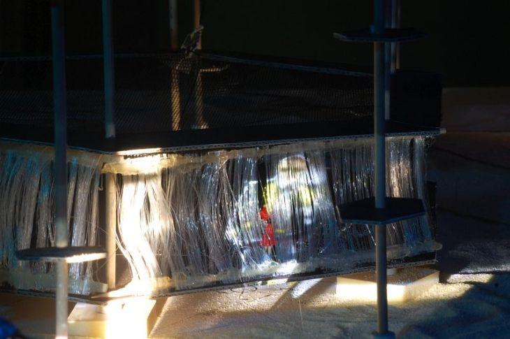 Während des Prozesses steigt Leontes den Kletterurm hinauf. Hermione ist auf der untersten Ebene des Turms und sieht nur die Projektion von Leontes auf der Wasserleinwand.